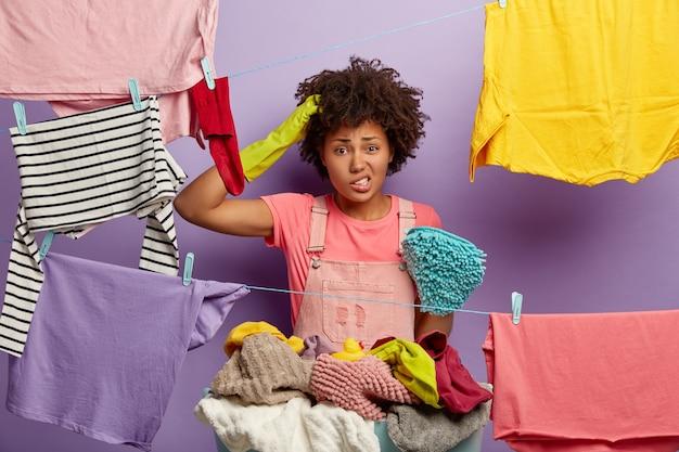 Verbaasde jonge vrouw met een afro poseren met wasgoed in overall