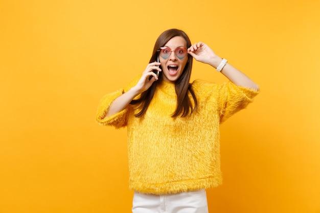 Verbaasde jonge vrouw met hartglazen praten op mobiele telefoon, aangenaam gesprek voeren geïsoleerd op felgele achtergrond. mensen oprechte emoties, lifestyle concept. reclame gebied.
