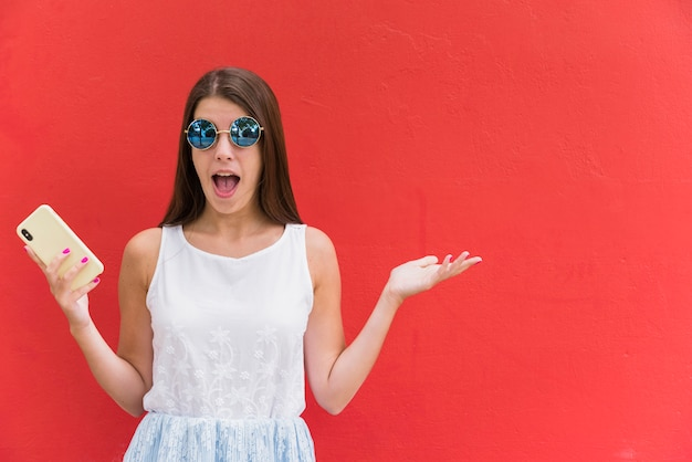 Verbaasde jonge vrouw met smartphone