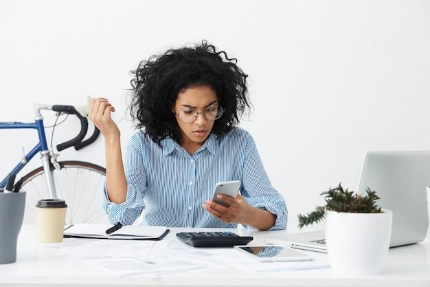Verbaasde jonge vrouwenwerknemer in formeel overhemd en ronde brillen met gefrustreerde blik