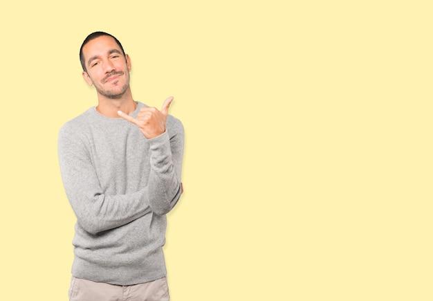 Verbaasde jongeman die een gebaar maakt van bellen met de hand