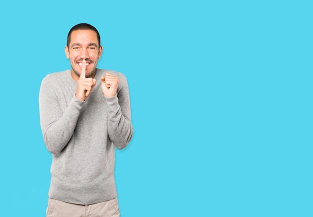 Verbaasde jongeman die om stilte vraagt terwijl hij met zijn vinger gebaart