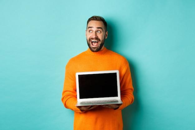 Verbaasde jongeman in een oranje trui die naar de linkerbovenhoek kijkt, met een aanbieding voor een laptopscherm, staande over een turkooizen achtergrond.
