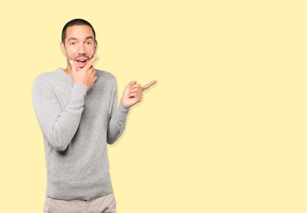 Verbaasde jongeman met een geschokt gebaar