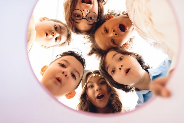 Verbaasde kinderen kijken samen in een ronde geschenkdoos.