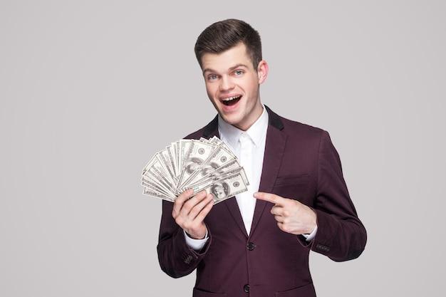 Verbaasde knappe brunette jonge zakenman in klassieke violette jas die staat, veel dollars vasthoudt, met de vinger wijst en naar de camera kijkt met open mond. indoor studio-opname, geïsoleerd, grijze achtergrond