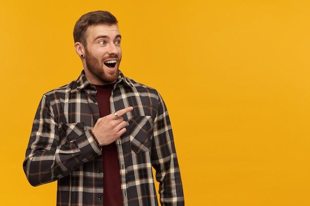 Verbaasde knappe jonge bebaarde man in geruit overhemd met geopende mond kijkt verbaasd en wijst met de vinger weg op de gele muur