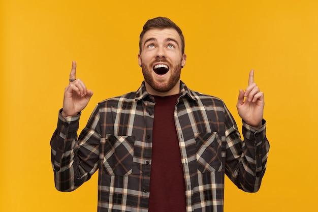 Verbaasde knappe jonge bebaarde man in geruit overhemd met geopende mond kijkt verbaasd en wijst met twee vingers omhoog naar de hemel over gele muur