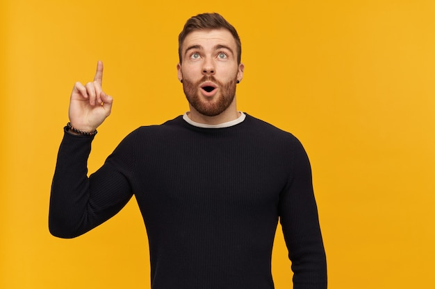 Verbaasde knappe jonge man met baard en geopende mond in zwarte longsleeve wijzend en kijkend naar de lucht over gele muur