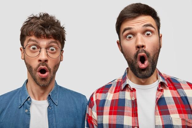 Verbaasde knappe jonge mannen laten hun kaken van verbazing vallen