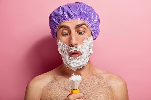 Verbaasde knappe man kijkt naar penseel, appiles scheergel, wil een gladde huid, heeft schoonheidsprocedures thuis, draagt een speciale hoed