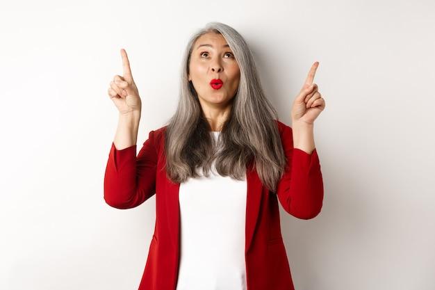 Verbaasde koreaanse zakenvrouw met grijs haar, gekleed in een rode blazer op het werk, wijzende vingers omhoog en kijkt verbaasd, staande op een witte achtergrond.