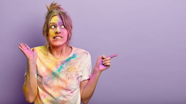 Verbaasde lieftallige europese vrouw bijt onderlip, wijst met wijsvinger naar lege ruimte opzij, demonstreert iets verbluffends, besmeurd met kleurrijk holipoeder. vrouw vuil door indiase kleurstoffen.
