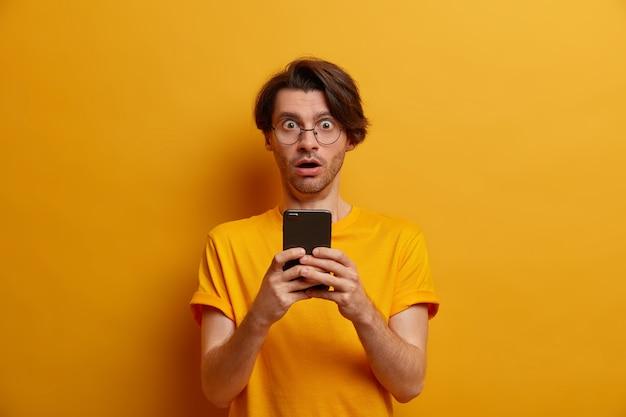 Verbaasde man afgeleid van het scherm van de smartphone, kijkt naar vreselijke video, hijgt naar adem van verwondering, kreeg onverwachte boodschap, draagt ronde sprectakels en t-shirt, geïsoleerd over levendig gele muur