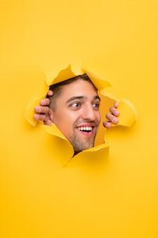 Verbaasde man die geel papier scheurt