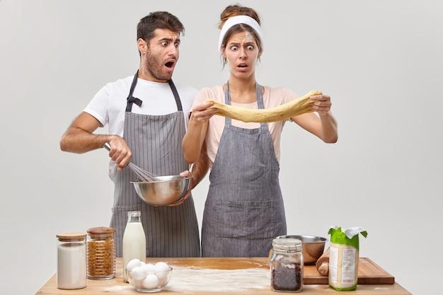 Verbaasde man en vrouw kijken geschokt naar rauw deeg, bereiden gebak, man zwaait ingrediënten in kom, weekend besteden aan koken thuis, poseren aan de keuken. culinair met eieren, bloem, melk