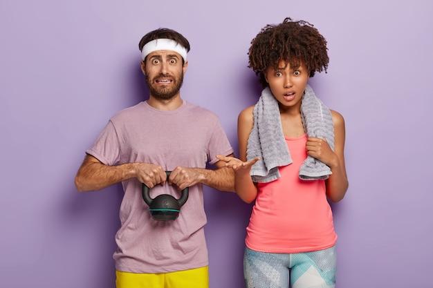 Verbaasde man houdt gewicht vast, gekleed in t-shirt en witte hoofdband en zijn gekrulde vrouw staat in de buurt, heeft een handdoek om de nek om het zweet af te vegen
