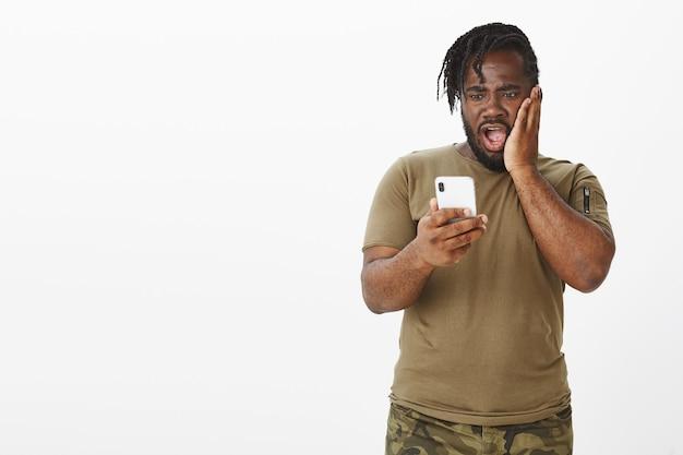 Verbaasde man in een bruin t-shirt die met zijn telefoon tegen de witte muur poseert