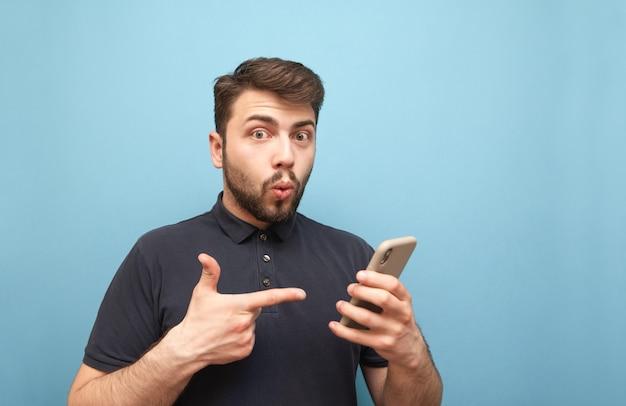 Verbaasde man in een donker t-shirt en baard, houdt een smartphone in zijn handen