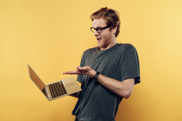 Verbaasde man in glazen kijken laptop scherm
