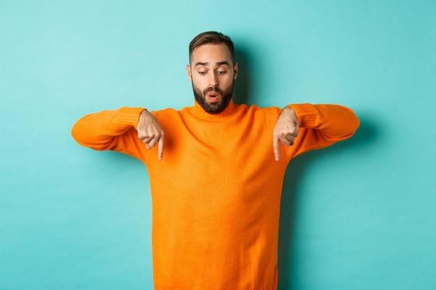 Verbaasde man in oranje trui, met de vingers naar beneden wijzend en met belangstelling naar promo, vakantiekortingen kijkend, staande over een turkooizen achtergrond