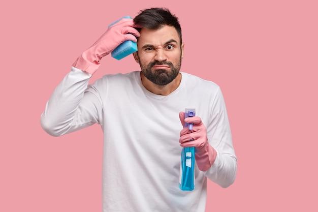 Verbaasde man krabt hoofd, kan niet beslissen wat hij eerst moet schoonmaken, houdt fles spray vast, zorgt voor hygiëne, draagt spons