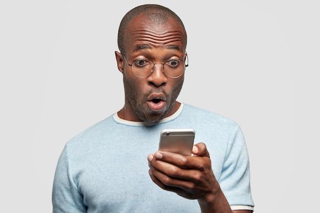 Verbaasde man leest tekstbericht met verbaasde uitdrukking, houdt mobiele telefoon vast, ontdekt iets schokkends