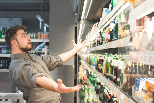 Verbaasde man met baard deed zijn handen open en wil al het bier in de supermarkt kopen.