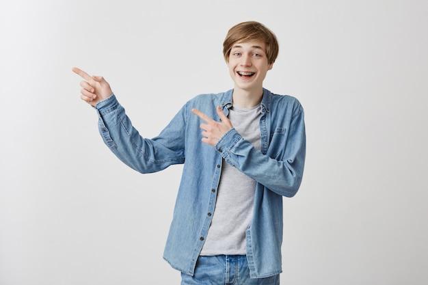Verbaasde man met blond haar en blauwe ogen steekt zijn vingers op, wijst naar boven als hij iets interessants ziet of adverteert dingen, zegt: kijk hier eens naar. mensen, positieve emoties, lichaamstaal