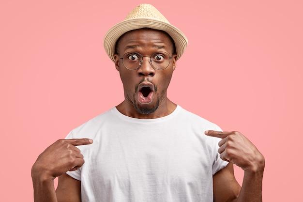 Verbaasde man met donkere huid wijst naar casual t-shirt, toont vrije ruimte voor uw advertentie-inhoud