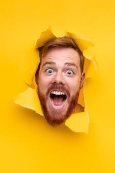 Verbaasde man met gemberbaard camera kijken en schreeuwen terwijl gluren uit gat in gescheurd geel papier