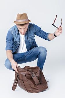 Verbaasde man met hoed kijkt in een lege leren tas dat het geld op is