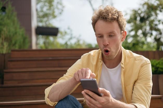 Verbaasde man met open mond die mobiele telefoon gebruikt om online op straat te winkelen