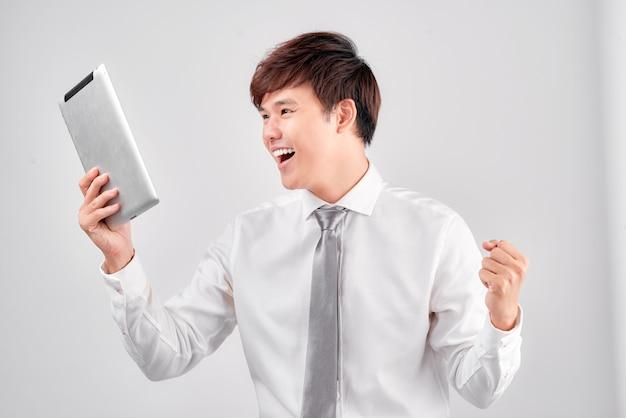Verbaasde man shopper consument verrast opgewonden door online overwinning geïsoleerd op wit