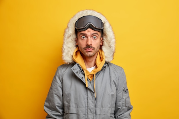 Verbaasde man snowboarder staart afgeluisterde ogen draagt warme winterjas met capuchon rust tijdens koude december kan niet geloven in iets ongelooflijks.