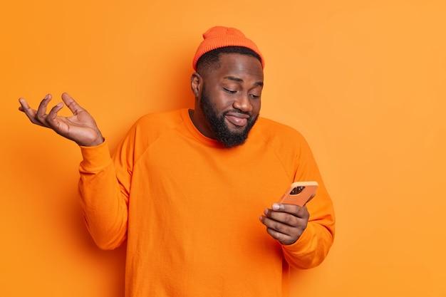 Verbaasde man steekt handpalmen op en gefocust op smartphonescherm kan niet begrijpen van wie hij bericht heeft ontvangen, draagt hoed en trui geïsoleerd over oranje muur