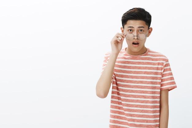 Verbaasde mannelijke aziatische student die bril opstijgt en kaak laat vallen terwijl hij naar indrukwekkend ding kijkt, zich geïnteresseerd voelt en verbaasd poseren onder de indruk