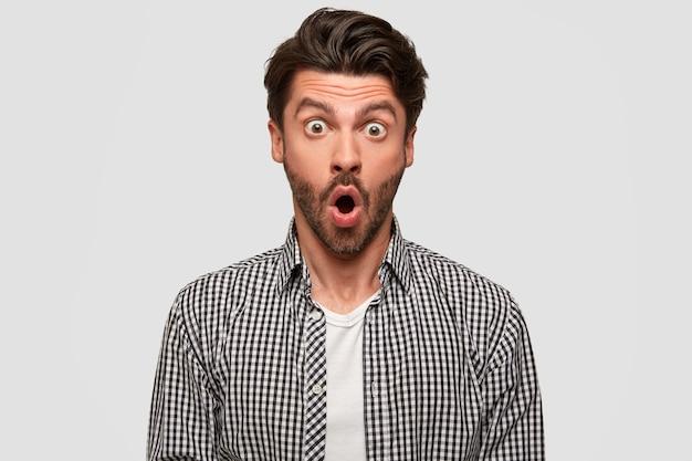 Verbaasde mannelijke kantoormedewerker heeft grote ogen en geopende mond, verbaasd gezicht, gekleed in een geruit overhemd, staat tegen een witte muur. mensen, reactie en shock concept. omg, wat ik zie!