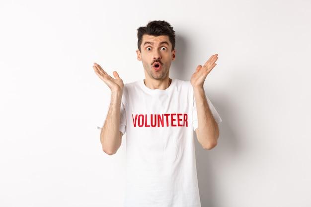 Verbaasde mannelijke vrijwilliger in wit t-shirt hoort geweldig nieuws, klapt in de handen en staart verbaasd naar de camera, poserend over studioachtergrond.