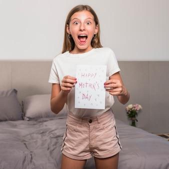 Verbaasde meisje met wenskaart met happy mothers day inscriptie