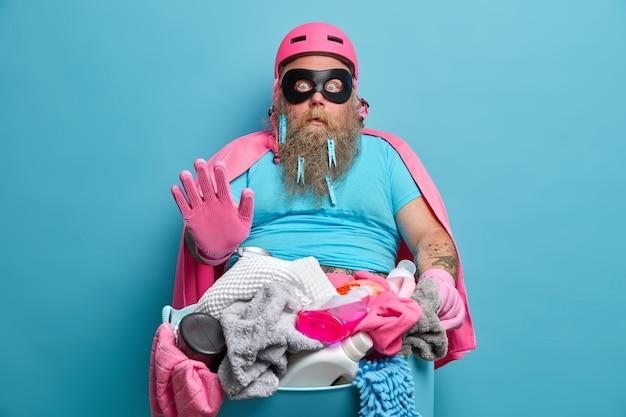 Verbaasde mollige man met dikke baard maakt stopgebaar maakt kleren klaar voor de was, gekleed in heldenmasker en cape dwazen rond