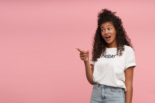 Verbaasde mooie jonge brunette donkerhuidige vrouw met lang krullend haar met wijsvinger opzij laten zien en verward wenkbrauwen optrekken, staande op roze in wit t-shirt en spijkerbroek