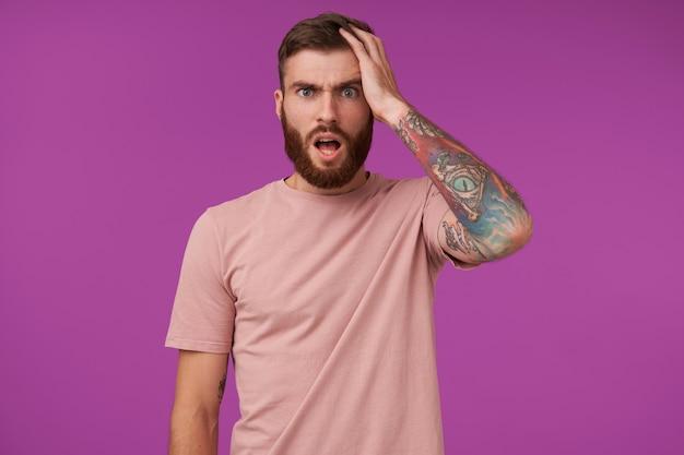 Verbaasde mooie jonge brunette man met baard en tatoeages fronsende wenkbrauwen met brede mond geopend en met opgeheven handpalm op zijn hoofd, staande op paars in beige t-shirt
