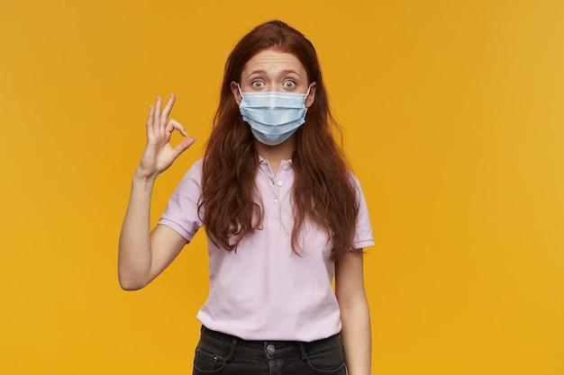 Verbaasde mooie jonge vrouw die een medisch beschermend masker draagt dat staat en een ok teken toont dat over een gele muur is geïsoleerd