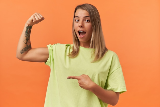 Verbaasde mooie jonge vrouw met geopende mond in gele t-shirt met biceps-spieren en erop wijzend geïsoleerd over oranje muur