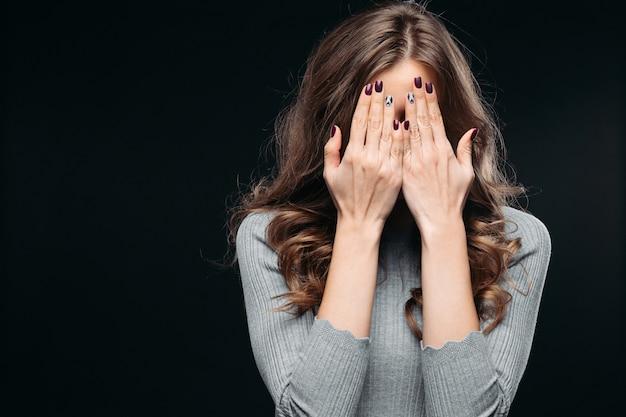 Verbaasde mooie vrouw die gezicht behandelt met hand