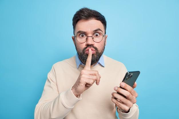 Verbaasde mysterieuze man maakt stiltegebaar vertelt geheime informatie gebruikt mobiele telefoon voor online chatten en werken op afstand draagt bril casual trui