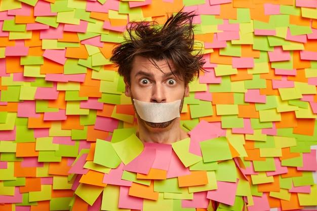 Verbaasde nerveuze man met plakband over de mond, vraagt stil te zijn, staat stil en sprakeloos, poseert tegen kleurrijke muur met plakbriefjes, bang. zwijg, censuur