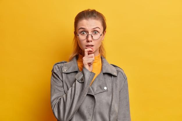 Verbaasde nerveuze student luistert aandachtig resultaten van examens, kijkt bezorgd, houdt de vinger op de lippen, draagt een transparante bril, grijze jas, schrikt om te spreken, heeft een verbaasde uitdrukking