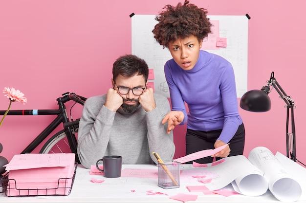 Verbaasde ontevreden bekwame vrouw en man werken samen aan ontwerpschetsen poseren in coworking-ruimte en maken blauwdrukken gekleed in vrijetijdskleding. gemengd ras collega's bereiden presentatie of project voor